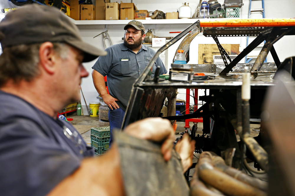 Elston Moore (left) and Mickey Burrell work on repairs for Burrell's racing car at a garage next to Moore's house in Springfield, Mo. on July 8, 2015. This was one of many repair sessions that week after a particularly bad race the previous Friday, where Burrell was part of a multiple car wreck that prevented him from finishing the race. This year has been one of disappointment for Moore and Burrell, as multiple wrecks and failures to finish have meant extensive repairs and little success to show for.