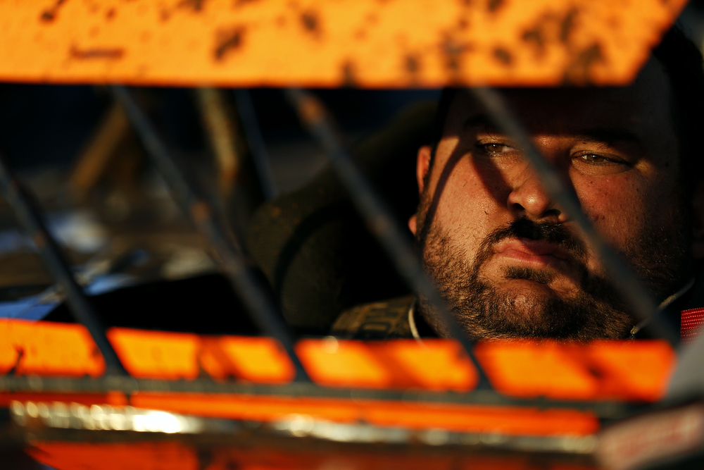 Mickey Burrell takes a moment in his car as he prepares to take the dirt track for a qualifying heat at the Springfield Raceway in Springfield, Mo. on June 21, 2015. Burrell would take first place in the qualifying heat, allowing him a start at the front of the pack during that evening's feature race.