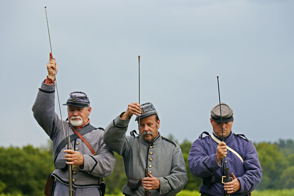 (from left) Rick Hardin of Bartlesville, Okla., Robert Serio of Neosho, Mo. and Matthew Frye of Bartlesville, Okla., playing members of the 3rd Louisiana Infrantry, load their muskets during living history demonstrations to commemorate the 154th anniversary of the Battle of Wilson's Creek at Wilson's Creek National Battlefield in Republic, Mo. on Aug. 8, 2015.