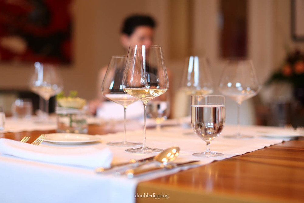 A carefully set table with elegant china and delicate wine glasses