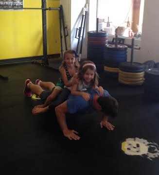 "Mark S. doing ""weighted"" push-ups with his daughters"