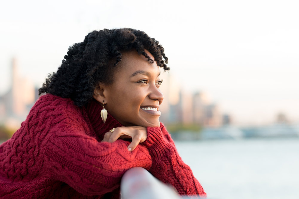 Woman recovered from mental health issue happily looking off into distance and smiling