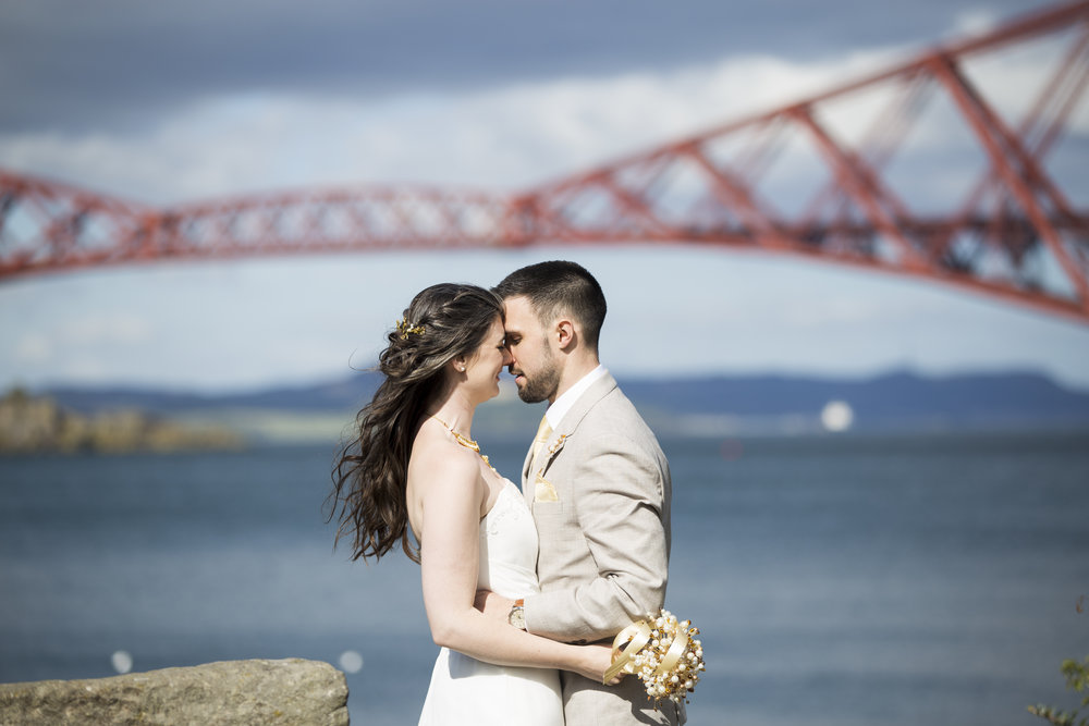 newly married couple embrace with the forth rail bridge in the background