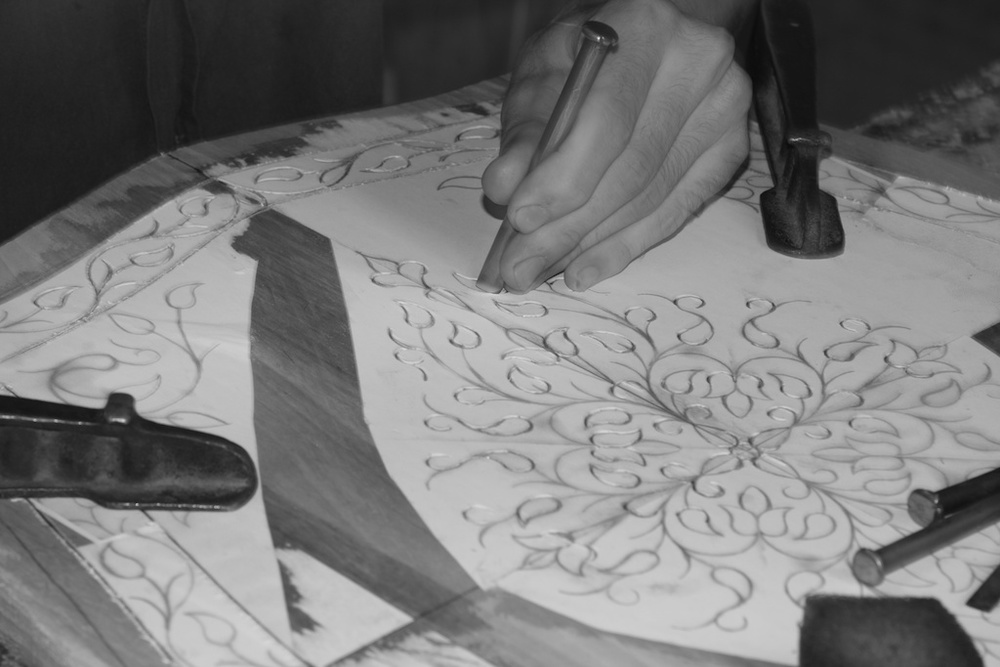 Patterns are applied by hand to the wooden surface