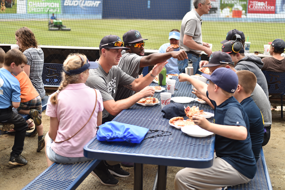 Children eat lunch at a Meet The Tourists event after participating in a free baseball clinic.  (Photo by board member Tony Farlow)