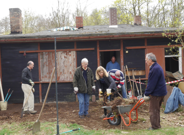 Frank Harding pushing wheelbarrow during Alexander Haus Clean-up Day, 5 April 2014
