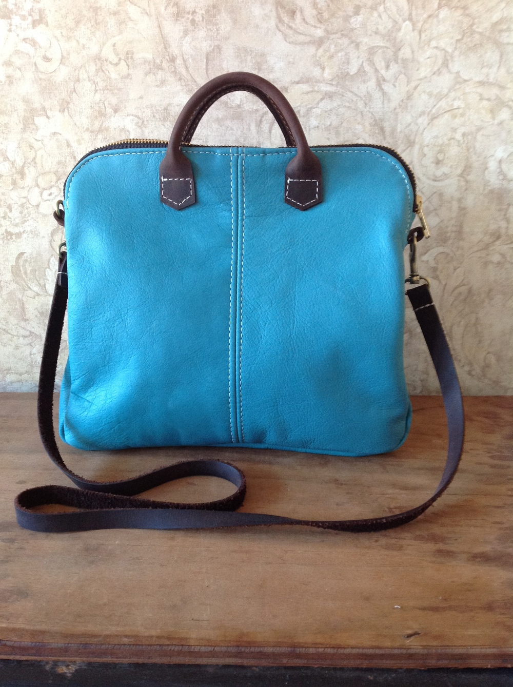 The Mini bag has a removable cross body strap, as well as, 2 small handles at the top.