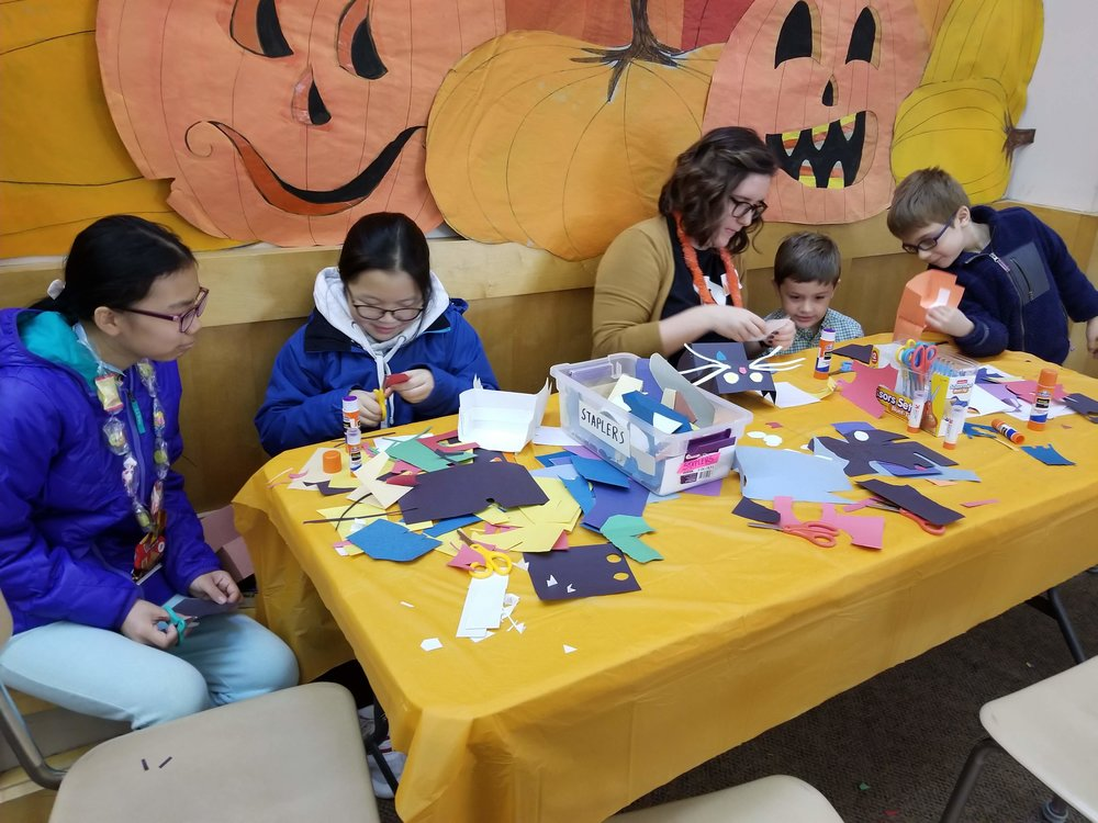 Box Office Associate Lakyn leading a puppet making craft at Lincoln School Pumpkinfest.