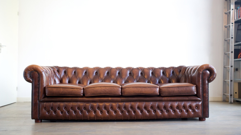 This couch has rolled arms with nailheads, a straight cushion, and square legs.