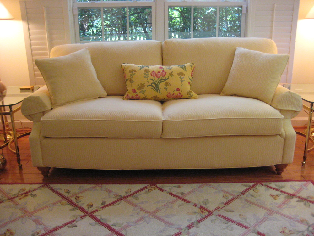 A sofa with bun feet, rolled arms, and a straight cushion.