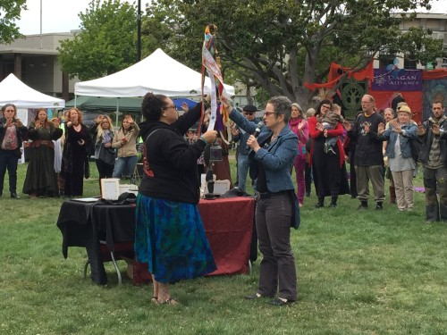 Crystal Blanton receives the Keeper of the Light staff from T. Thorn Coyle at the 2015 Pagan Festival