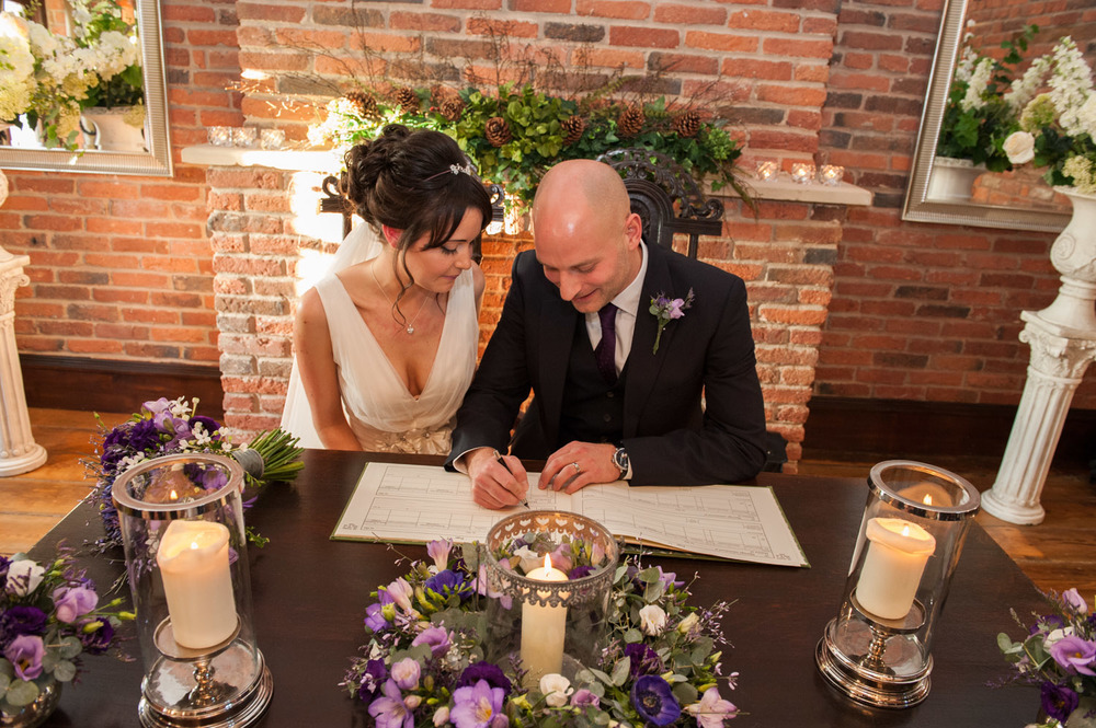 bride and grrom signing the register at Swancar Farm
