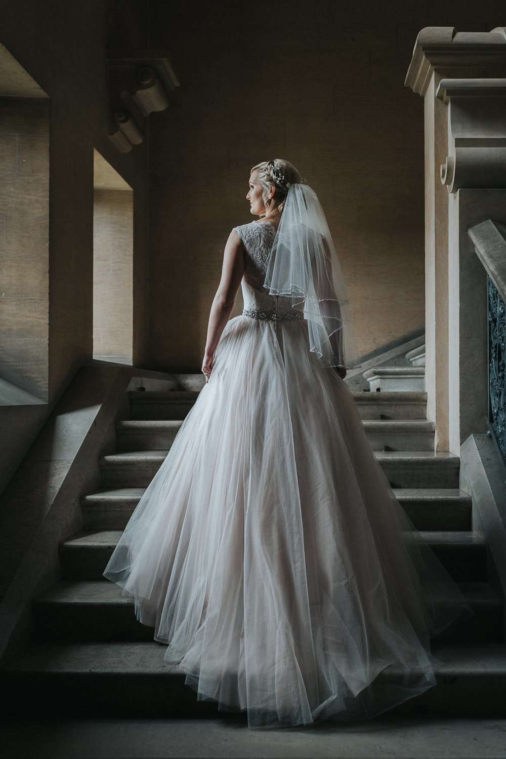 bride on the stairs at Harlaxton Manor wedding