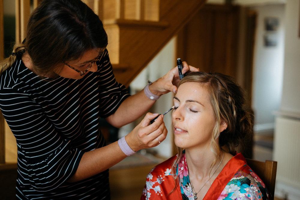 bride getting her wedding makeup applied