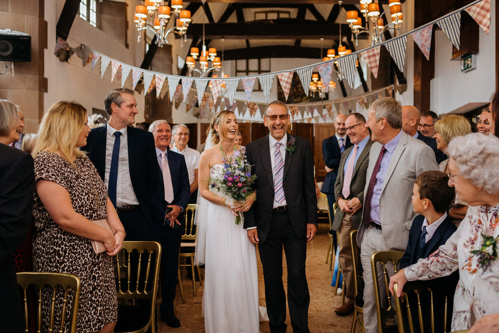 Father and the bride walking down the aisle at Risley Hall