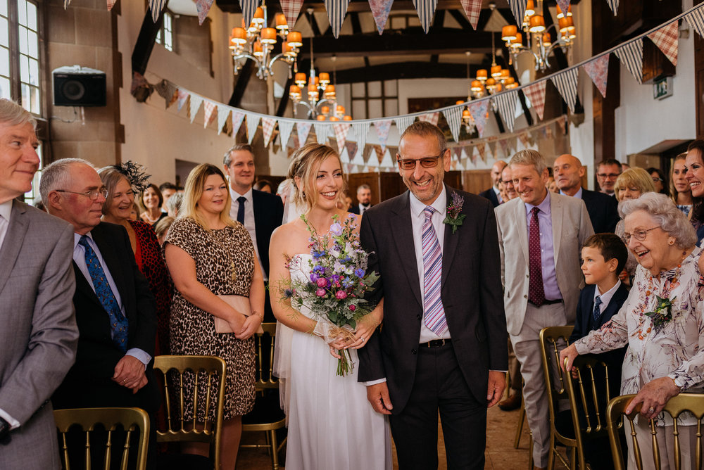 The bride and her father waslking down the aisle at Risley Hall