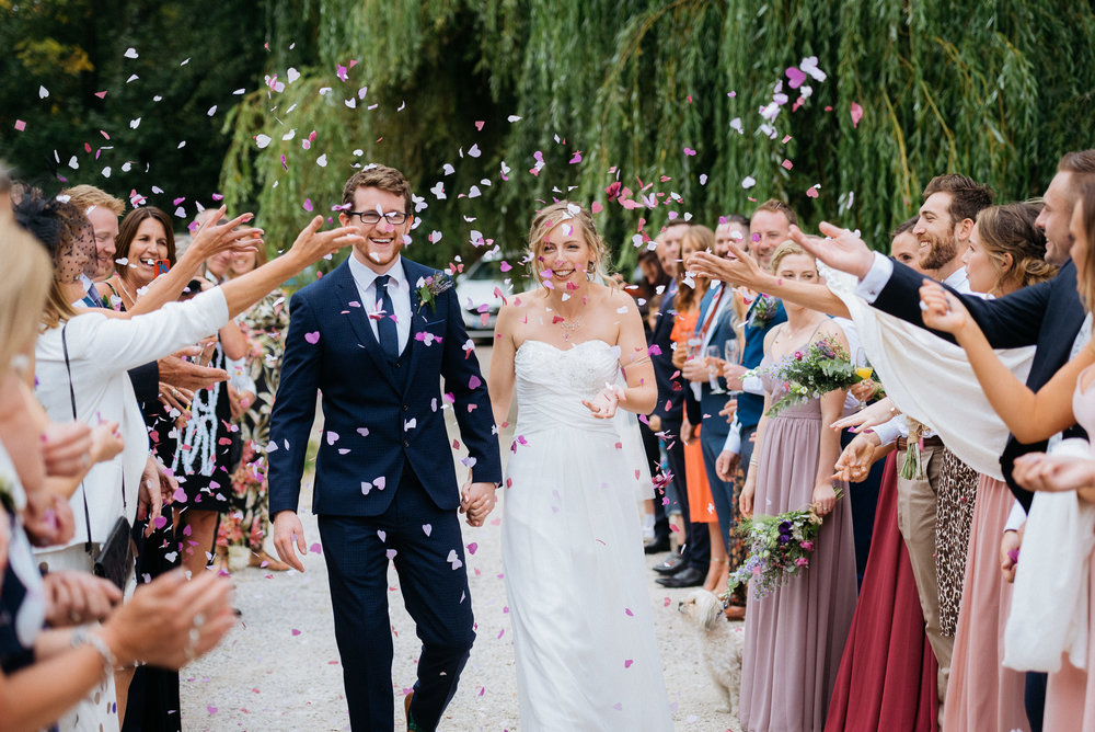 Bride and groom loving the confetti being thrown over them at Risley Hall