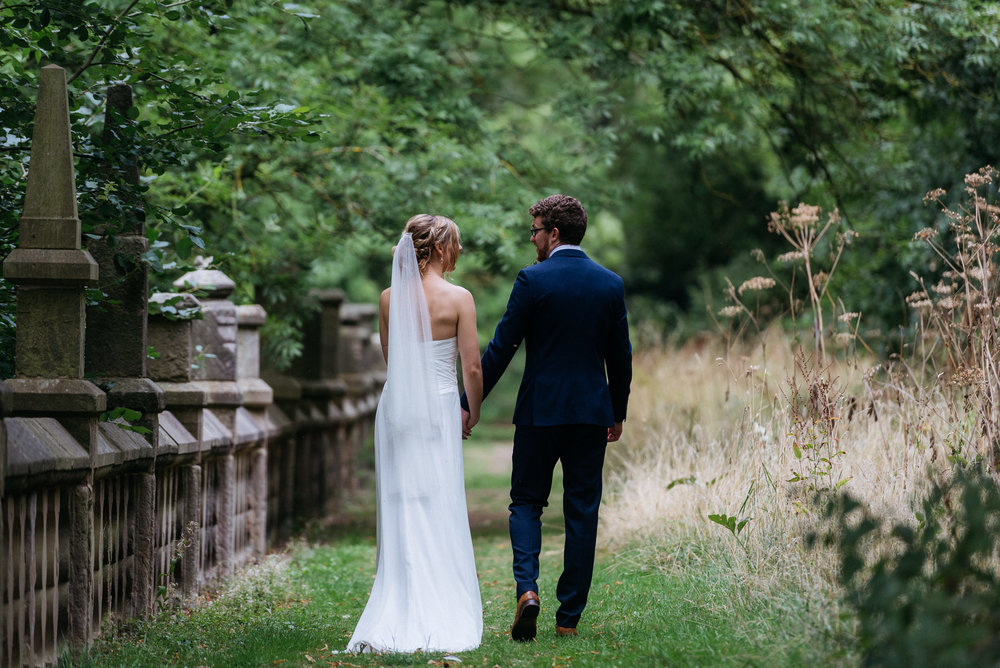 Bride and groom taking a private walk at their wedding at Risley Hall