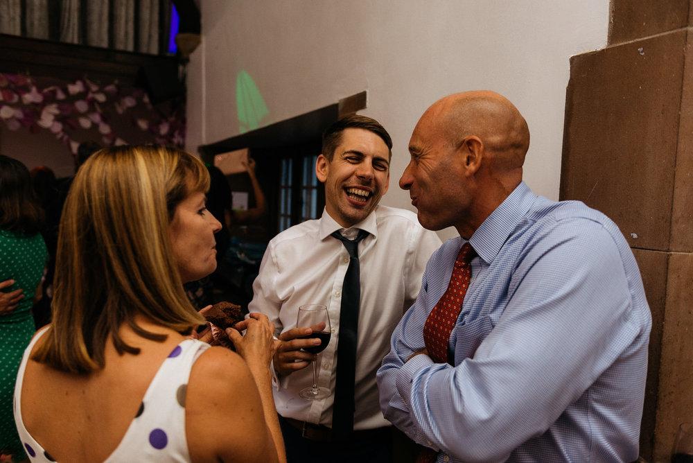 wedding guests sharing a joke.