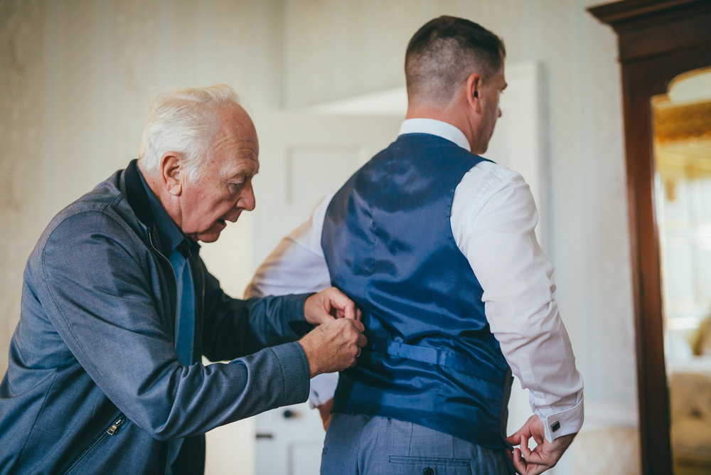 Groom having his waist coat tightened