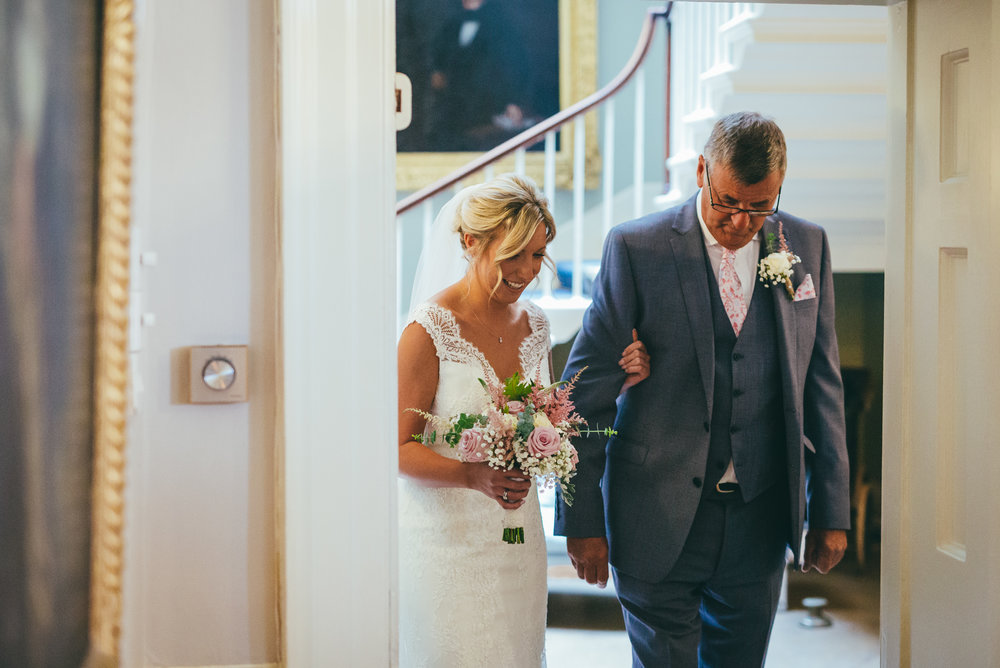bride and her father walking into the ceremony room