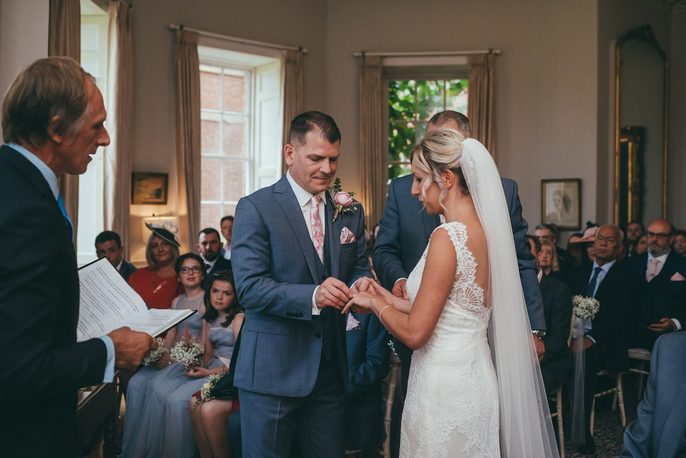 Groom putting on his brides wedding ring during the ceremony