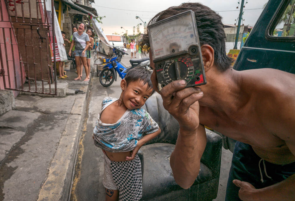 A junkman and his son walk the street picking up discarded items. As they see me approach with my camera, the junkman quickly pulls out a broken meter that he has in his bag so that he can pretend he is taking my picture. -- Manila, Philippines