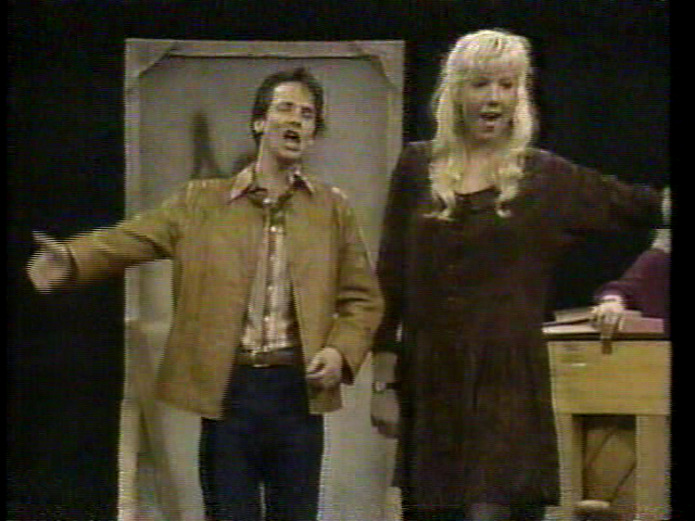 "Recurring characters Manfred (John Cameron Mitchell) and Monica (Kirsten Holmquist) performing ""White Boys"" in a style that presages the singing music teachers from SNL"