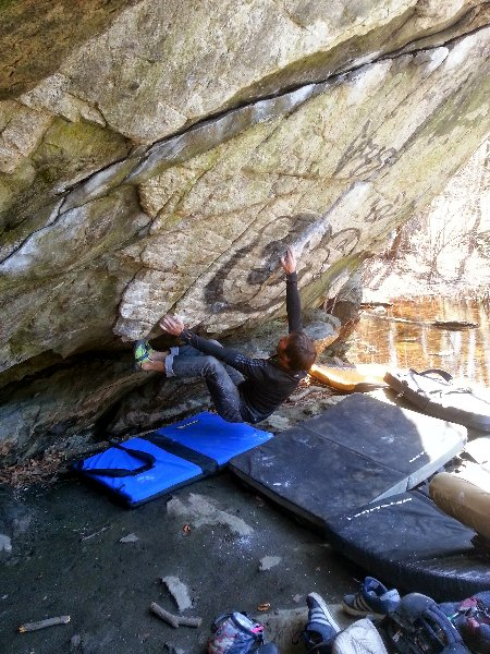 Kevin Joregeson attempting Under the Grid, V10, in the Pond Cave at Lincoln Woods, RI. Photograph by Joe McLoughlin