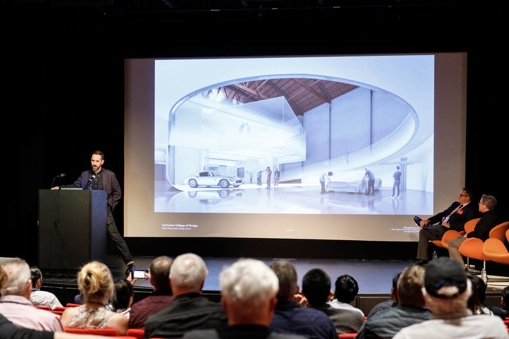 Architect Darin Johnstone presenting during a 2018 Alumni Reunion panel at ArtCenter's Ahmanson Auditorium about the future Mullin Transportation Design Center