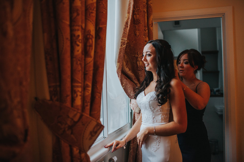 Bride standing at window getting helped into dress