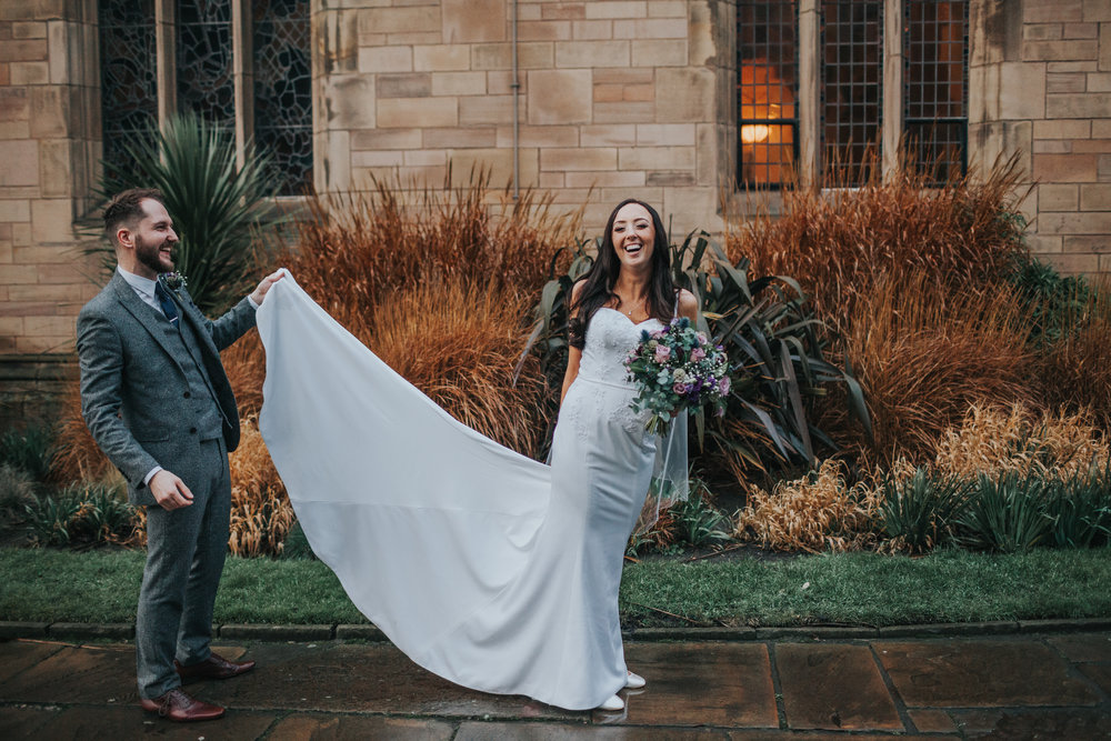 Bride laughs as groom fixes dress