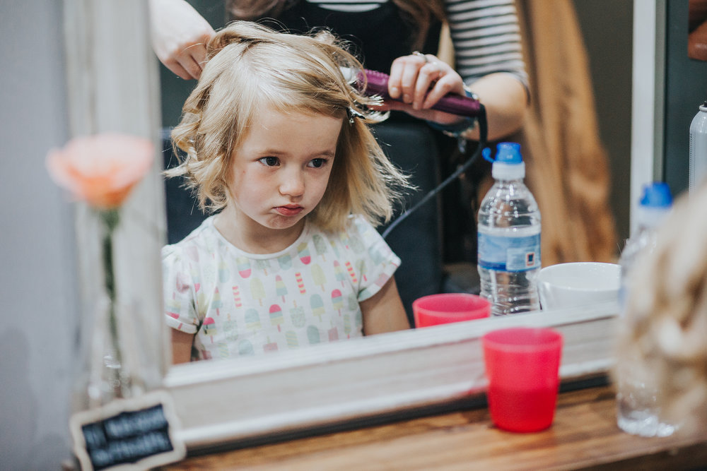 Grumpy cute child gets hair done, while looking very grumpy