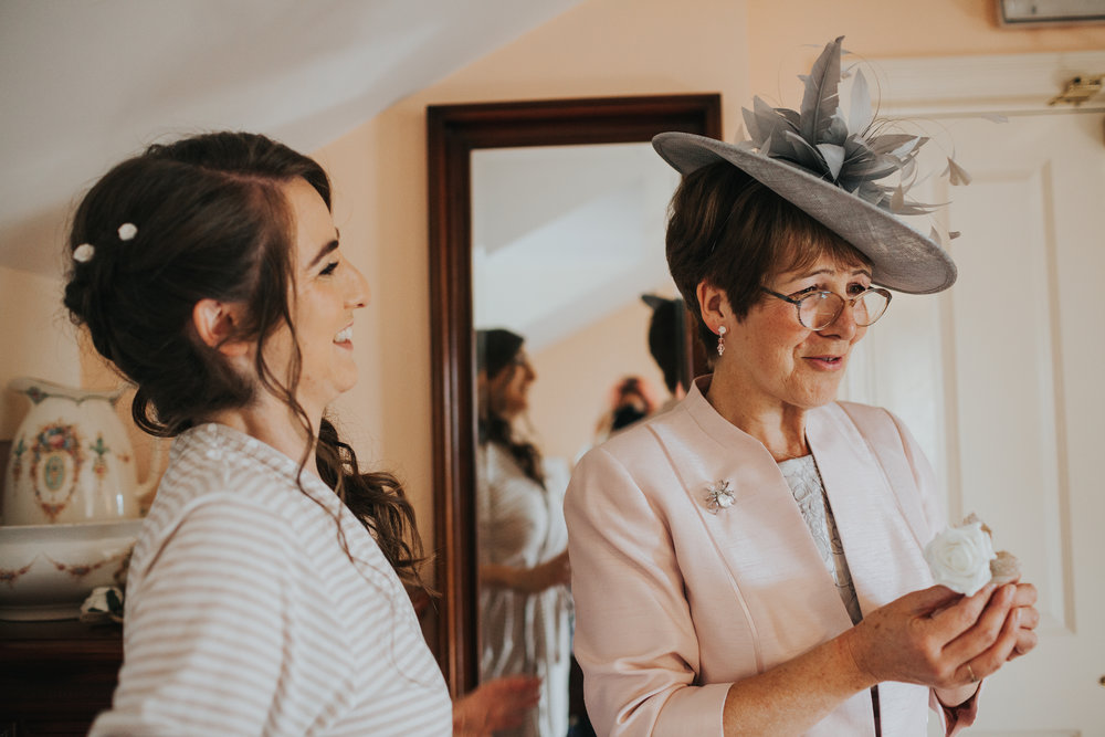 Bride laughs at Mum. Mum wears nice hat.
