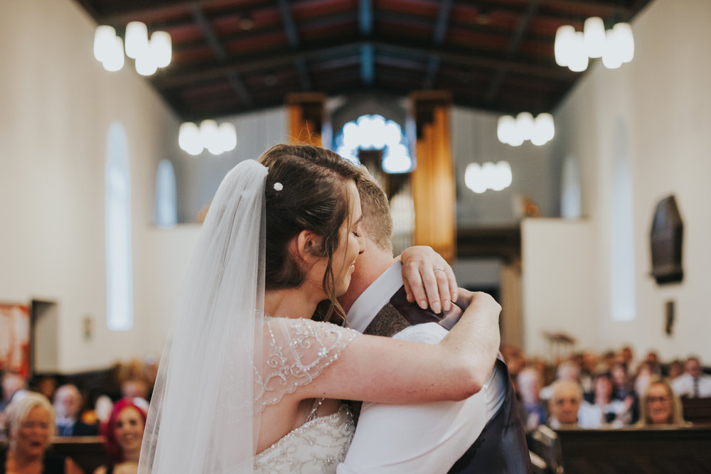 Husband and Wife embrace in church (beautifully captured in a more or less symmetrical shot by photographer)