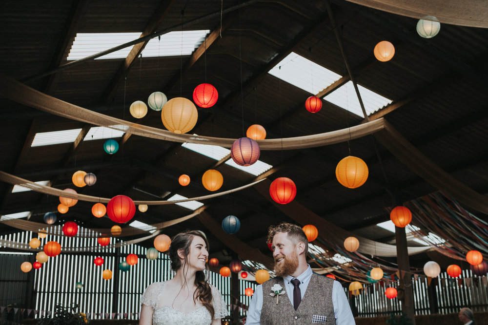 Bride and Groom stand together in front of room full of colourful lanterns