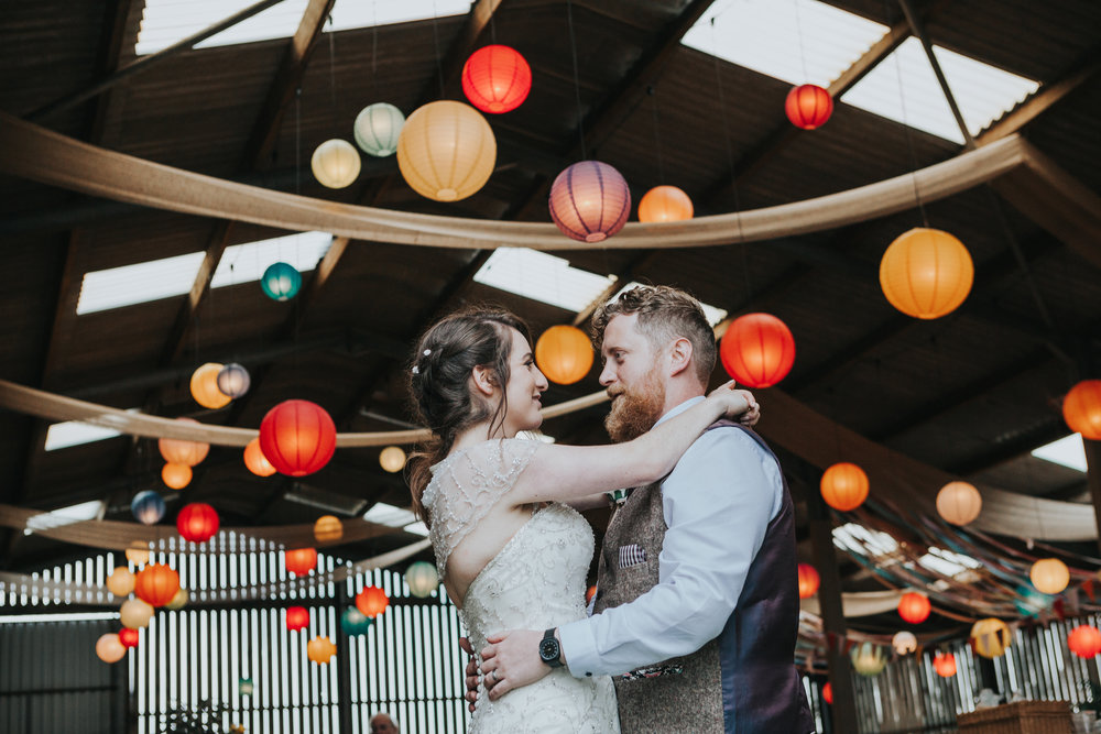 Rachel and Matthew stand together in front of room full of colourful lanterns
