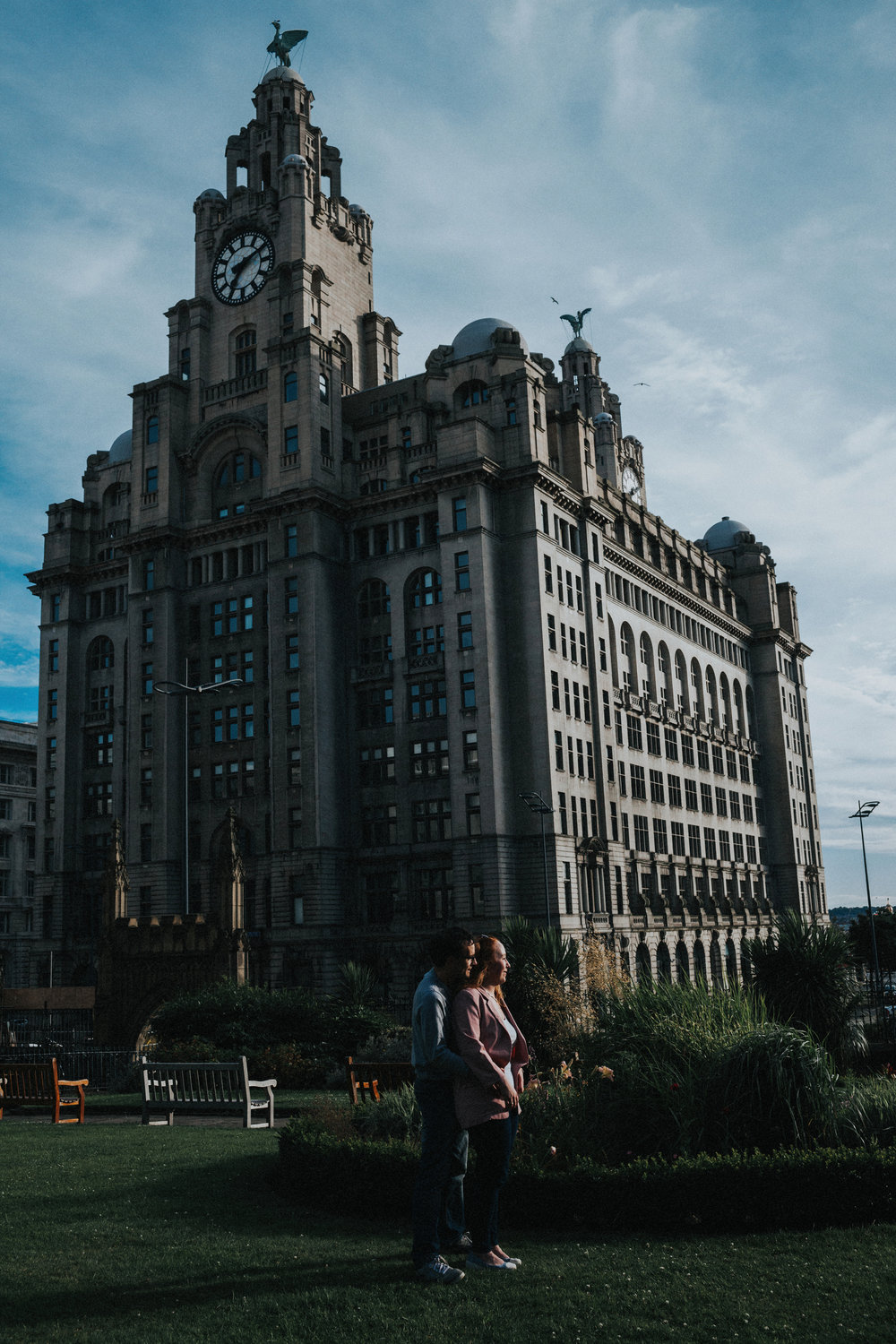 Sun hits couple in front of Liver Buildings