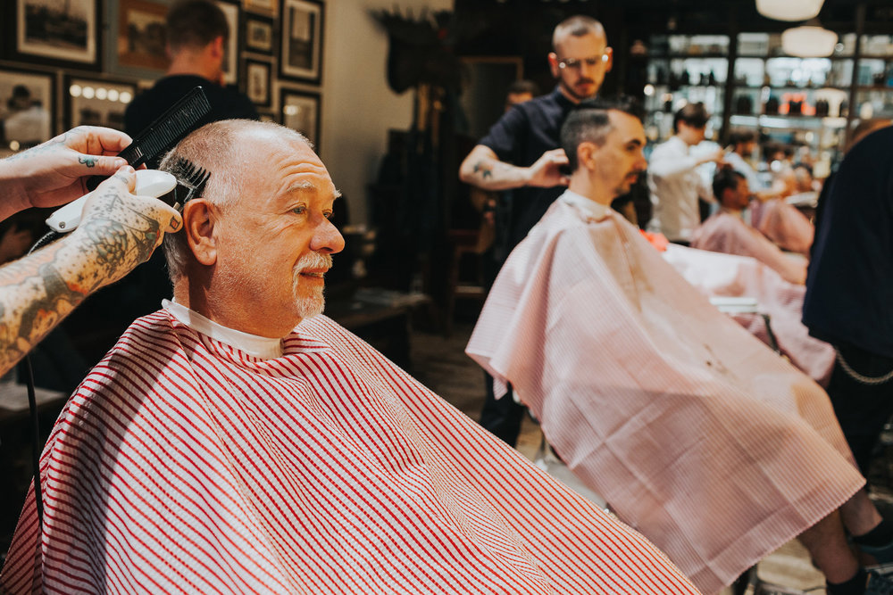 Groomsman getting hair cut with clippers, Manchester