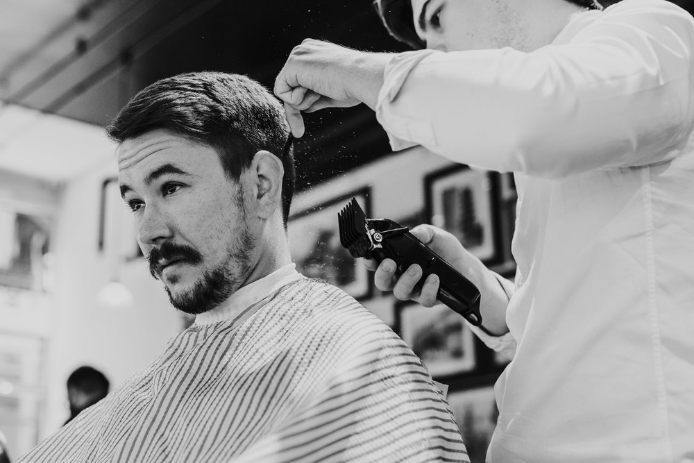 Black and white photograph of groom getting hair shaved.
