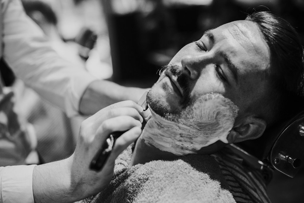 Groom getting cut throat shave, black and white photograph
