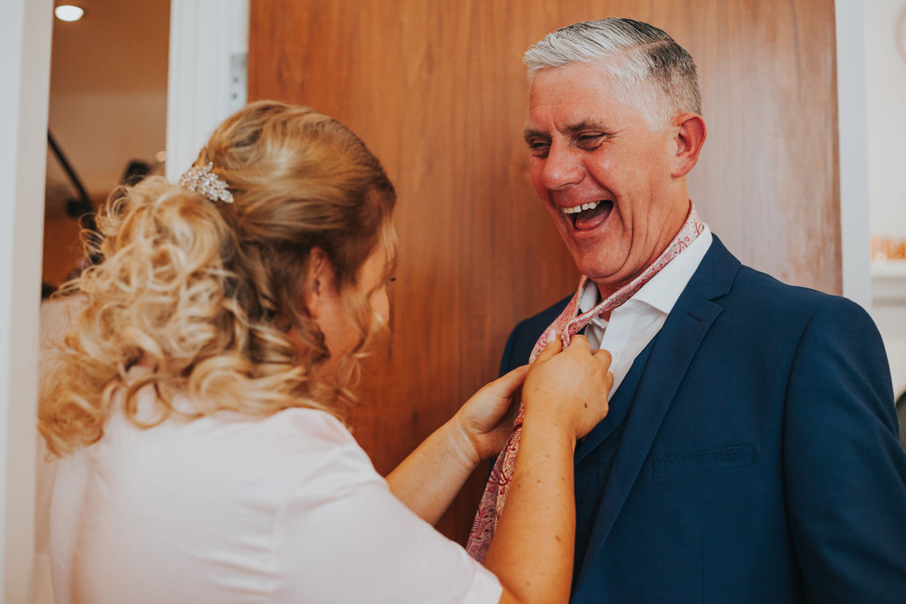 Father of the bride getting his suit fixed and laughing