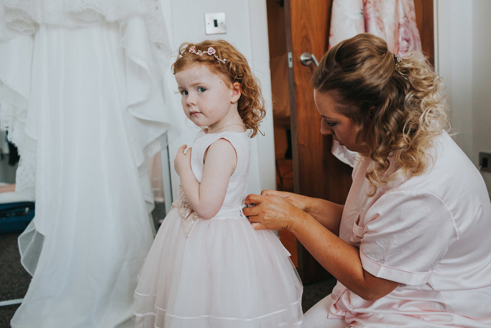 Flower girl had her buttons done up by bridesmaid, the brides wedding dress hangs in the background.