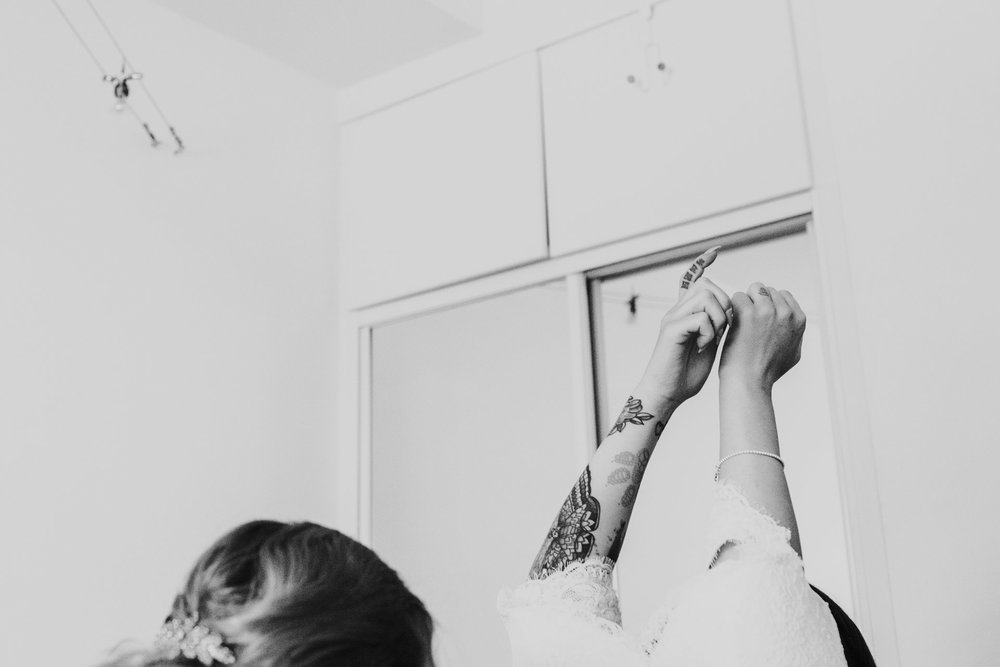 Brides tattooed arm reaches up as she puts on her wedding dress. Image processed in black and white