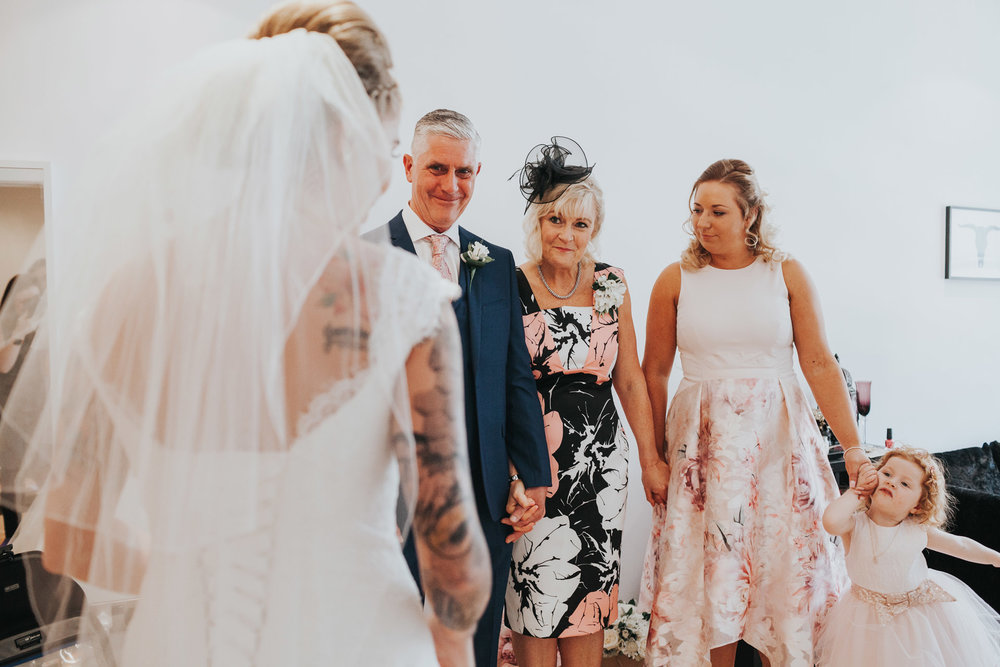 Bride comes out to see her family in her wedding dress.