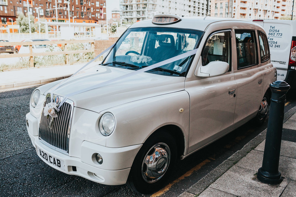 White taxi awaits bridal party.