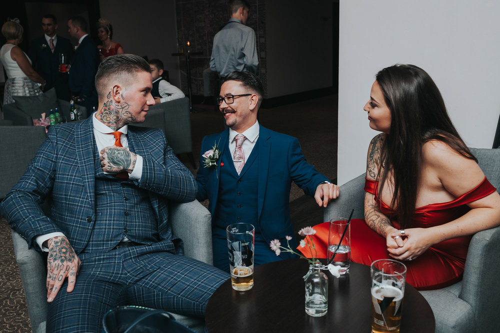 The groom laughs with friends.