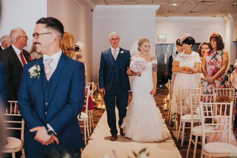 Bride walks down the aisle with her father looking excited.