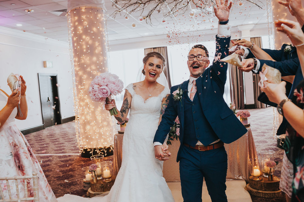 Bride and groom laugh as guests throw confetti.