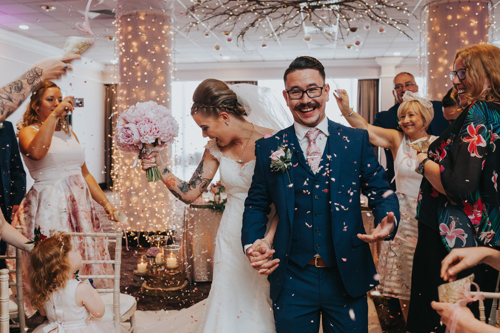 Guests throw confetti as bride and groom walk down the aisle.